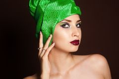 Beautiful girl with fashion turban on her head. Beautiful brunette girl with fashion green turban on her head Royalty Free Stock Image
