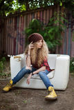 Beautiful girl in fashionable clothes on a broken couch. Beautiful girl in fashionable clothes on broken couch Stock Photography