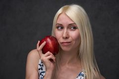 Beautiful girl in a fashionable dress with apple. Portrait composition royalty free stock images