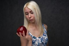 Beautiful girl in a fashionable dress with apple stock images