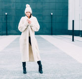 Beautiful girl in a fashionable white coat and knit posing on the street Stock Image