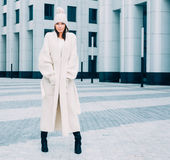 Beautiful girl in a fashionable white coat and knit posing on the street. Srteetstyle. Outdoor. Royalty Free Stock Photography