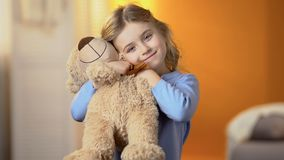 Beautiful girl with favourite teddy bear toy smiling at camera, happy childhood royalty free stock photo