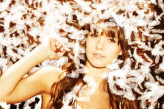 Beautiful girl with feathers. Lovely young woman surrounded by floating white feathers Stock Photo