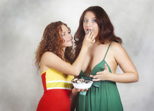 Beautiful girl feeds cookie its girlfriend royalty free stock photos