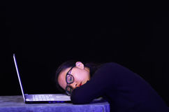 Beautiful girl fell asleep over her laptop wearing her glasses on dark background.  Stock Photos
