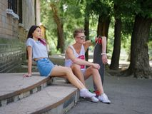 A beautiful girl and a fellow with a longboard sitting on stone stairs on a natural blurred background. Royalty Free Stock Images