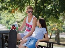 A beautiful girl and a fellow talking on a bench, a cute couple of teens dating in a park, on a natural blurred Royalty Free Stock Images