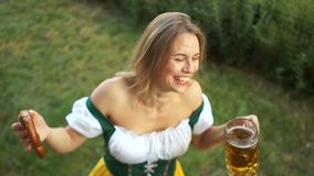 Beautiful girl at the festival festival Oktoberfest. The woman is dressed in Bavarian traditional clothes, drinks beer. And laughs cheerfully. Top View stock video