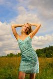 Beautiful girl on the field. And blue cloudy sky behind her Royalty Free Stock Images