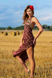 Beautiful girl in the field. Of haystacks royalty free stock photo
