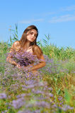 The beautiful girl is in the field covered with flowers Stock Image