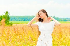 Beautiful  girl in a field with gold ears of wheat Stock Image