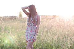 Beautiful girl field green meadow in summer park delicate dress, enjoying leisure, fashion style, glamor life,  student. Beautiful girl in the park in the summer Royalty Free Stock Photo