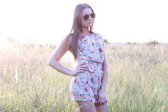 Beautiful girl field green meadow in summer park delicate dress, enjoying leisure, fashion style, glamor life,  student. Beautiful girl in the park in the summer Stock Images
