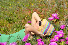 Beautiful girl on a field with pink flowers. On a warm summer day Stock Photo