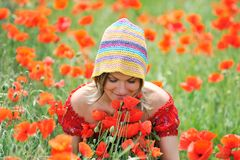 Beautiful girl on a field with poppies. Smelling flowers Royalty Free Stock Images