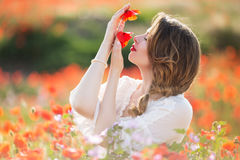 Beautiful girl in field of poppy flowers, spring time Stock Photos