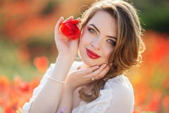 Beautiful girl in field of poppy flowers, spring time Royalty Free Stock Photography