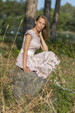 Beautiful girl in the field. Women sits on a rock, enjoying the outdoors and the sun. Royalty Free Stock Images