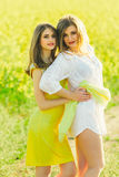 2 beautiful girl in a field of yellow flowers.Mom with daughter or two sisters hugging against the background of a field Royalty Free Stock Photo