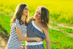 2 beautiful girl in a field of yellow flowers.Mom with daughter or two sisters hugging against the background of a field Stock Photography