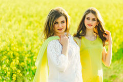 2 beautiful girl in a field of yellow flowers.Mom with daughter or two sisters hugging against the background of a field Royalty Free Stock Images