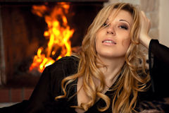 Beautiful girl by the fireplace Stock Image