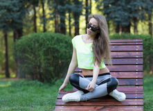 The beautiful girl fitness model sits in sunglasses on a wooden chair in park. Short top sports pants. Fitness abs Royalty Free Stock Images