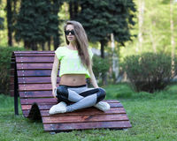 The beautiful girl fitness model sits in sunglasses on a wooden chair in park. Short top sports pants. Fitness abs Stock Photos