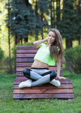 The beautiful girl fitness sit in a wooden chair. Short top sports pants. Stock Photo