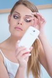 Beautiful girl fixing her eye lashes. By using her phone as a mirror Stock Photo