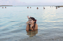 Beautiful girl floated in the Dead Sea. The beautiful girl floated in the sea in the evening on the Dead Sea Stock Image
