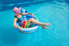 Beautiful girl floating in the swimming circle in the pool in summer Royalty Free Stock Image