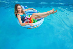 Beautiful girl floating in the swimming circle in the pool in summer Stock Photo