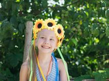 Beautiful girl with floral decoration fun glances to the side. Portrait of beautiful girl with flowers of sunflowers on his head. The concept of a happy Royalty Free Stock Image