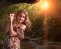 Beautiful girl in floral dress in forest. Stock Photos
