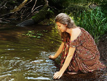 Beautiful girl in floral dress looks at his reflection in the water Stock Photos