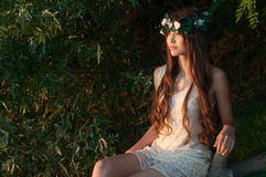Beautiful girl in floral wreath is sitting outdoors. Beautiful girl in floral wreath is sitting outdoor, the style of spring and summer Stock Photo