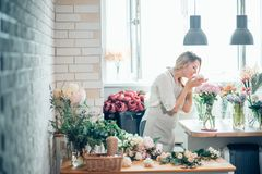 Beautiful girl florist with closed eyes smiling sniffing bouquet flowers royalty free stock photos