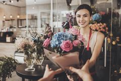 Beautiful girl florist sends bouquet to the buyer. Smiling young girl florist giving a bouquet of flowers to the buyer. A beautiful bouquet of flowers make a royalty free stock image