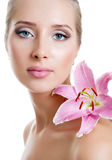 Beautiful girl with a flower lily. The face of a beautiful girl with a fresh flower lily Royalty Free Stock Image