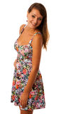 Beautiful girl in flower patern short summer dress posing against white Stock Photography