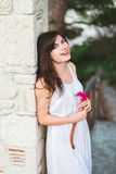 A beautiful girl with a flower in a wihite dress. At a column royalty free stock photos