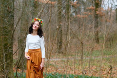 Beautiful girl with flower wreath on her head in the autumn forest Stock Photo