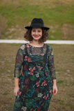 Beautiful girl with flowered dress an black hat Royalty Free Stock Image