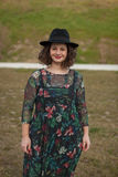 Beautiful girl with flowered dress an black hat Royalty Free Stock Images