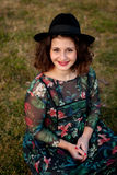 Beautiful girl with flowered dress an black hat Stock Photos