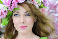Beautiful girl in a flowered garden peach Stock Photos