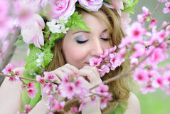 Beautiful girl in a flowered garden peach Stock Photo